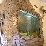 стена в комнате отделанная природным камнем, аквариум